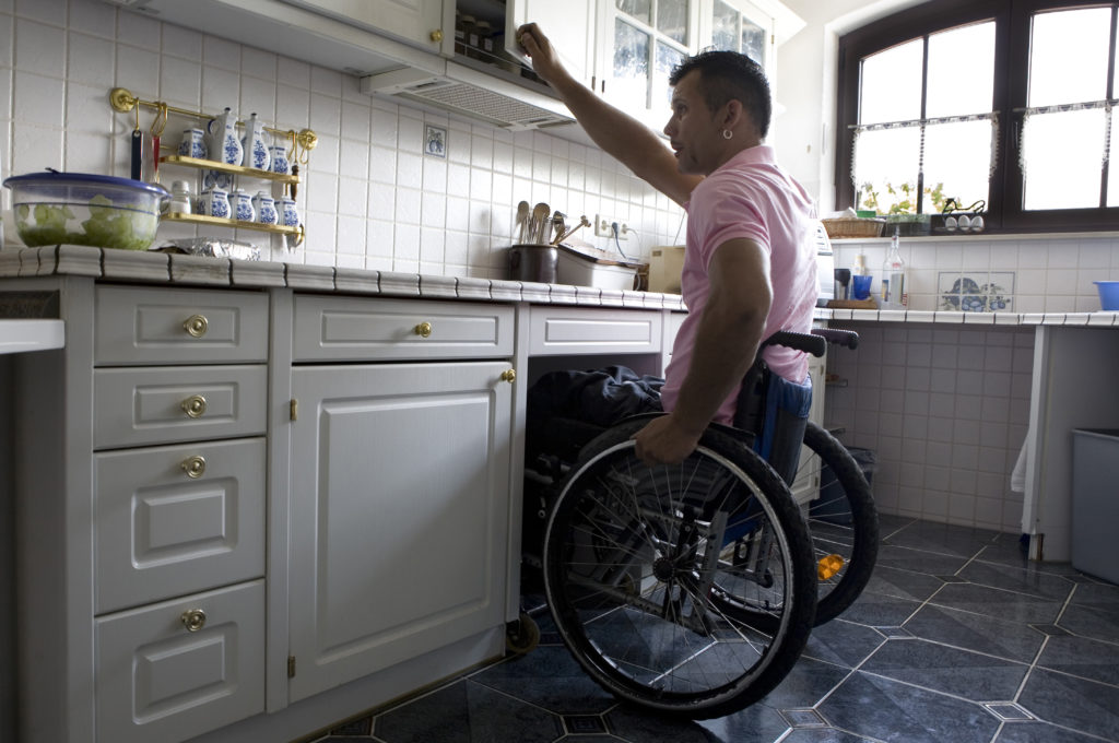 A young latino man in a wheelchair in his kitchen, with accessible features.