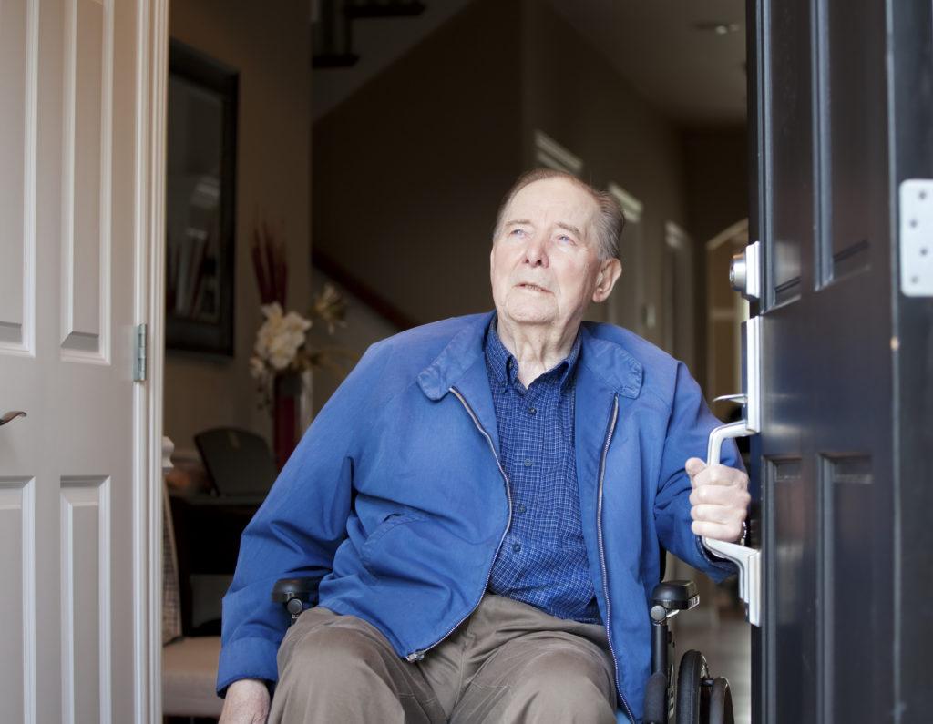 Elderly man in wheelchair at his front door, looking up towards sky