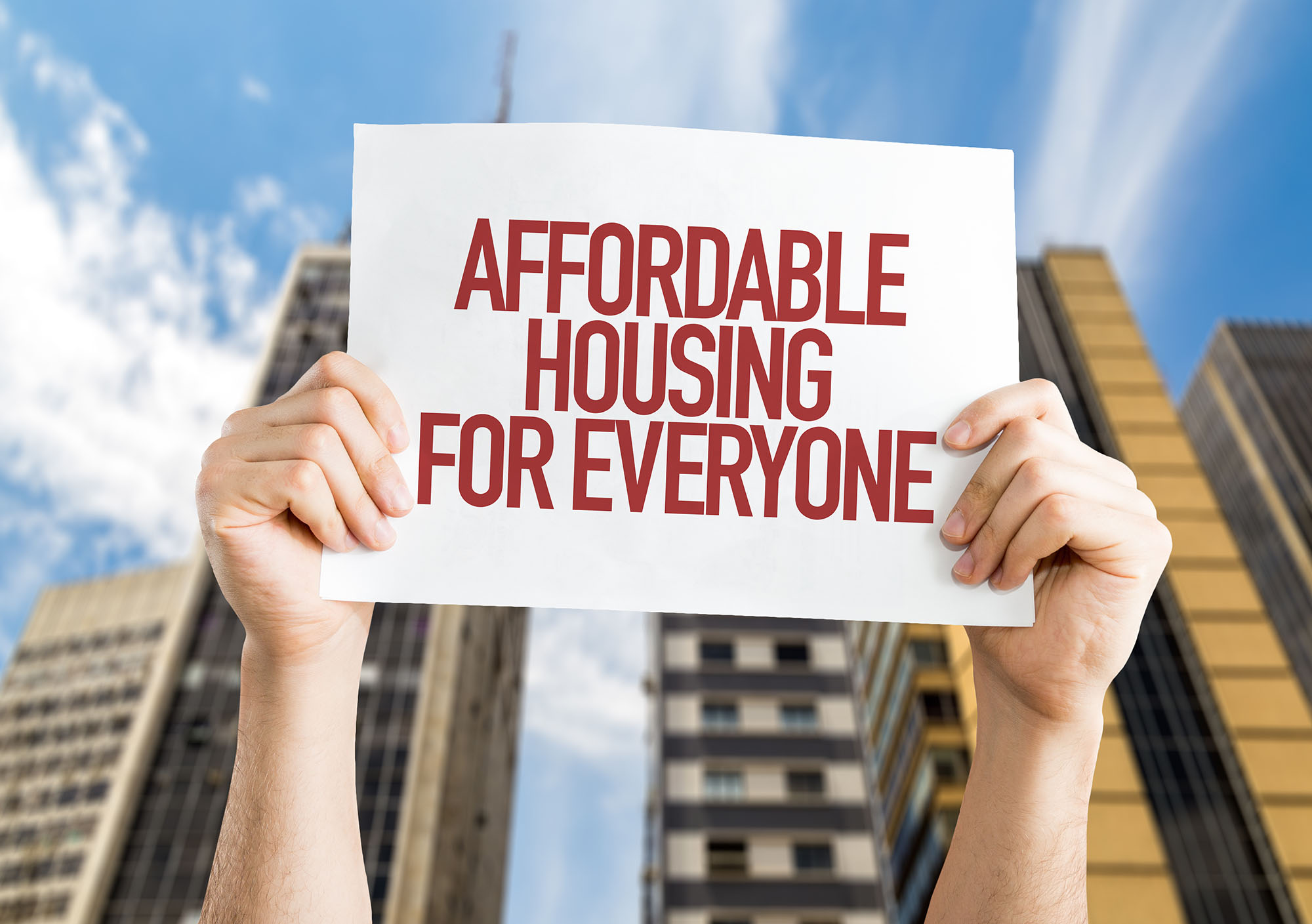 """A sign that says """"Affordable Housing for Everyone"""" being held up by two hands with a blue sky and buildings in the background"""