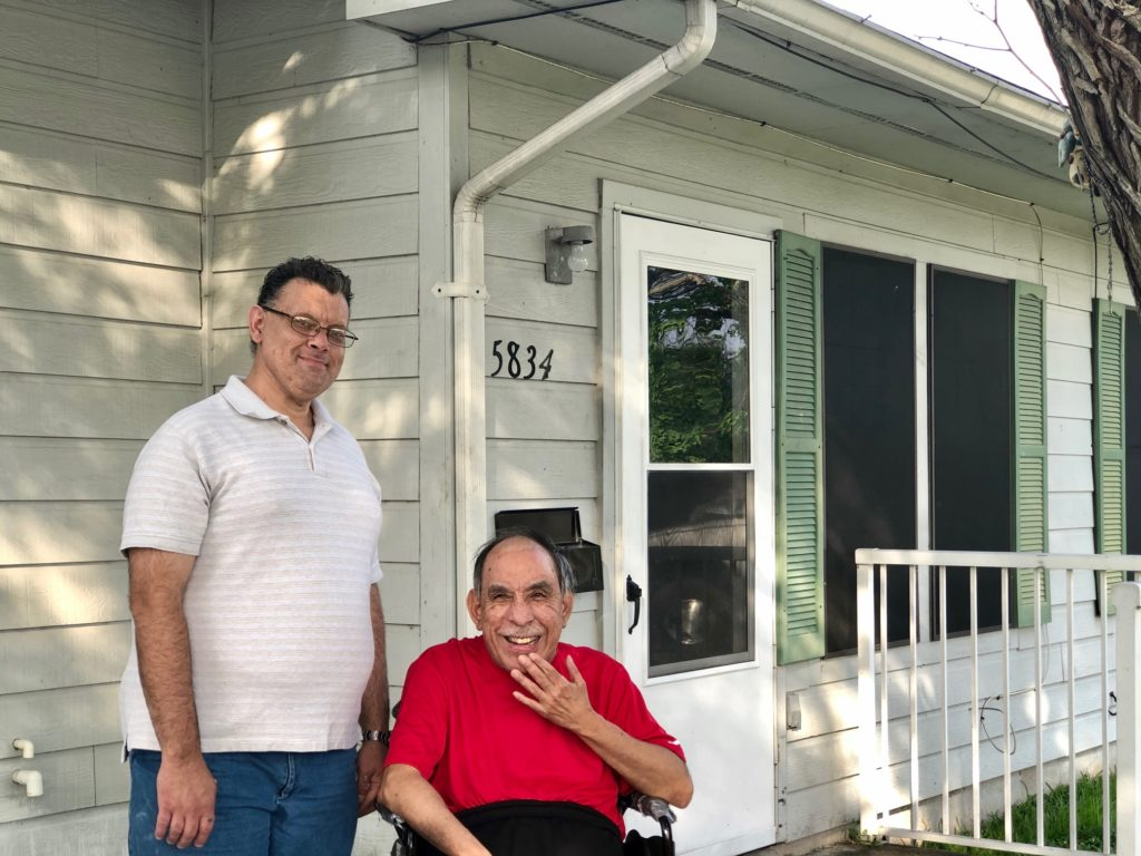 A man in a white shirt with glasses and a man in a wheelchair in a red shirt standing in front of a house.