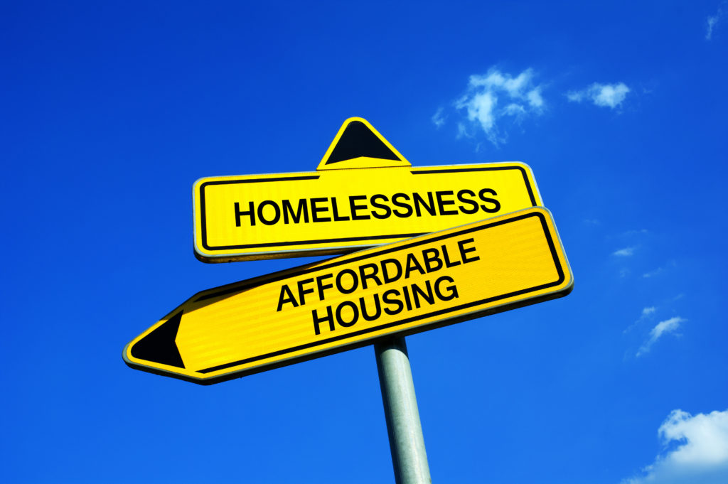 """A yellow sign surrounded by blue sky that reads """"Homelessness"""" with an arrow pointing in one direction, """"Affordable Housing"""" with an arrow pointing in another"""