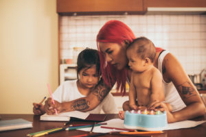 A young Latina mother with a baby and a toddler sitting at a table working on homework