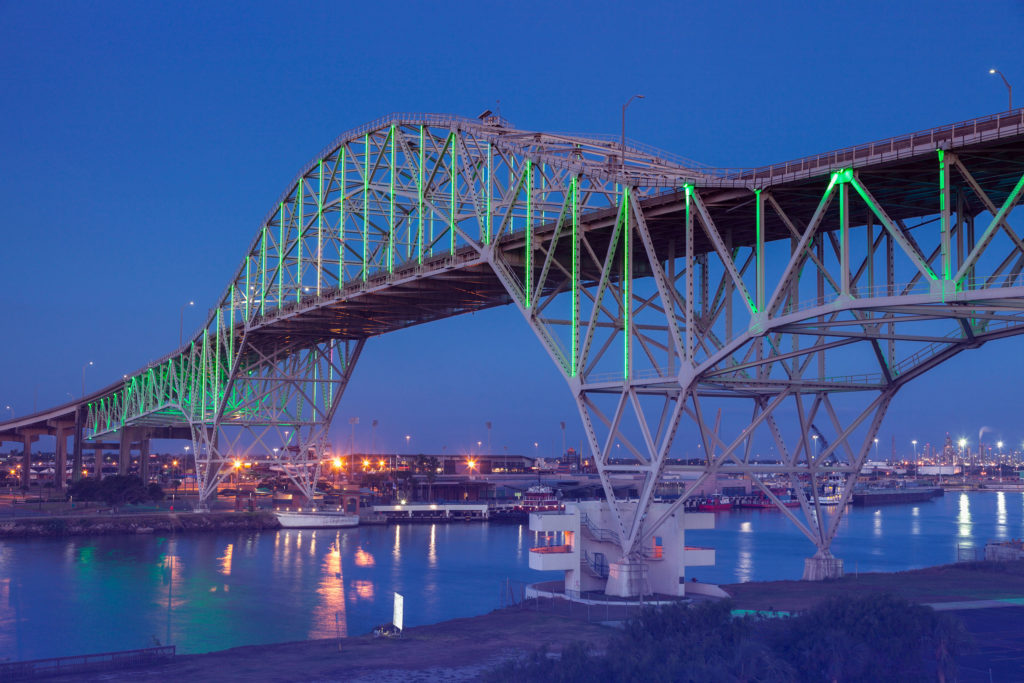 The Corpus Christi Harbor Bridge at dusk, with green lights reflecting on the water below.